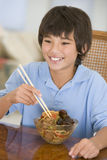 Young boy in dining room eating chinese food Stock Images