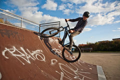 Young boy with dirtbike in halfpipe. Boy is biking with the dirtbike in a bike park at the halfpipe Royalty Free Stock Image