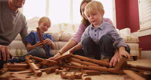 Young boy disassembling wooden play house Royalty Free Stock Images