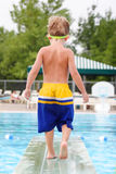 Young boy on a diving board. A young boy walks out onto a diving board ready to dive into the pool Stock Photo
