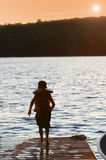 Young boy on a dock at sunset Stock Images