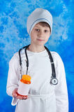 Young boy in doctor's costume holding pills bottle Royalty Free Stock Photos