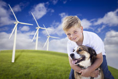Young Boy and Dog in Wind Turbine Field. Handsome Young Blue Eyed Boy and Dog Playing Near Wind Turbines and Grass Field Stock Photo