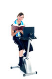 Young boy doing fitness and studying. Young teenager boy doing fitness on home-trainer with laptop and books, studying Royalty Free Stock Photos