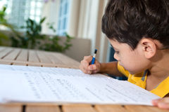 Young boy doing his homework. In a home environment stock photo