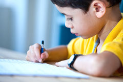 Young boy doing his homework. In a home environment royalty free stock photography
