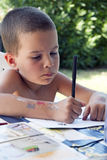 Young boy doing his homework. Portrait of a cheerful young boy doing his homework in the garden Stock Photography