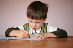 Young boy doing his homework at home. Write something in his notepad royalty free stock photography