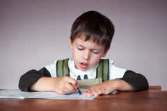 Young boy doing his homework at home. This image has attached release stock images