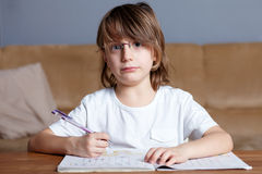 Young boy doing his homework, sitting at table. Young boy sitting at table doing his homework stock photography