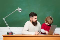 Young boy doing his school homework with his father. Teacher helping young boy with lesson. Little students. Daddy and royalty free stock image