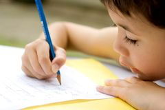 Young boy doing homework. Young boy concentrating on his writing homework from school, enjoying it outdoors Royalty Free Stock Photos