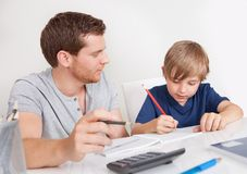 Young boy doing homework. Together with his father Royalty Free Stock Photo