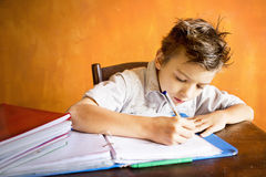 A young boy is doing homework. A young boy is doing and concentrating  on homework Stock Image