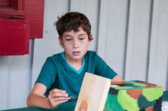 Young boy doing a painting craft Royalty Free Stock Image