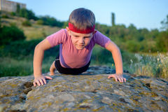 Young boy doing push-ups on a rock Stock Photography