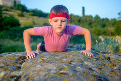 Young boy doing push-ups on a rock Royalty Free Stock Images