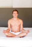 Young boy doing spiritual moves on bed Royalty Free Stock Photography