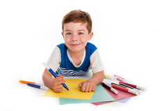 Young Boy Drawing on Colored Paper. Smiling young boy with felt pens writing and drawing on  colourful paper. White background Stock Photos