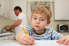 Young boy drawing while father works in kitchen Royalty Free Stock Photos