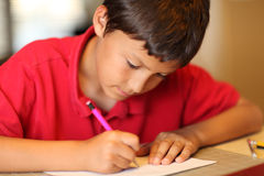 Young boy drawing for homework Stock Image