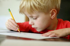 Young Boy Drawing with Pencil. A young, preschool aged child is drawing on a white piece of paper with a writing pencil Stock Image
