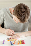 Young Boy Drawing on White Paper with Crayons Stock Image