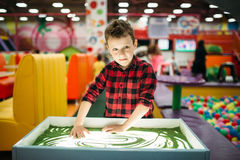 Young boy draws in the sand, entertainment center Royalty Free Stock Images