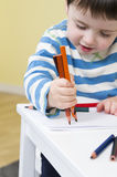 Young boy draws with three pencils stock photography