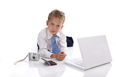 Young boy dressed as businessman with gadgets. Young boy dressed as businessman with electronic gadgets - isolated on white Royalty Free Stock Photography