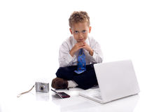 Young boy dressed as businessman with gadgets. Young boy dressed as businessman with electronic gadgets - isolated on white royalty free stock images
