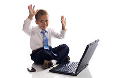Young boy dressed as businessman with laptop. Young boy dressed as businessman works on his laptop computer - isolated on white stock images