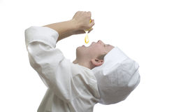 Young boy dressed as chef squeeze fresh lemon juice on white bac Stock Images