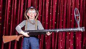 Young Boy Dressed as Clown Holding Oversized Rifle Royalty Free Stock Photography