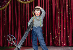 Young Boy Dressed as Clown Holding Oversized Rifle Stock Photography