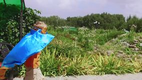 Young boy dressed as superhero playing outdoors