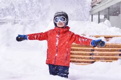 Happy young boy standing in the snow at ski