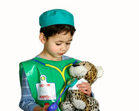 A young boy dressing up as a doctor. Pretending to check on his patient, a stuff leopard Stock Images