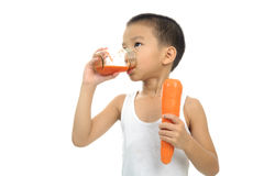 Young boy drink carrot juice Royalty Free Stock Photos