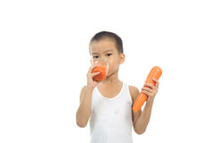 Young boy drink carrot juice Royalty Free Stock Images