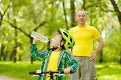 Young boy drink water is learning to ride a bike with his grandfather royalty free stock photos