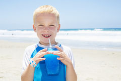 Young boy drinking a blue ice drink at the beach during summer vacation Stock Images