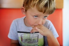 Young boy drinking from glass of fresh water. In restaurant Royalty Free Stock Photos
