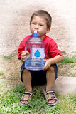 Young boy drinking from a large jug of water after outdoor activ Royalty Free Stock Photography