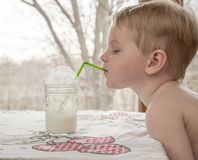 Young boy drinking milk. And blowing milk bubbles through a straw stock photos
