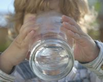 Young boy drinking water. A young boy is drinking a tall glass of water Royalty Free Stock Images