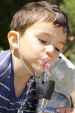 Young boy drinking from water fountain Stock Images