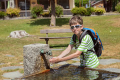 young boy is drinking water from a fountain Stock Photo