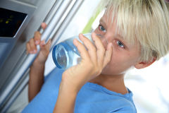 Young boy drinking water. From fridge stock images