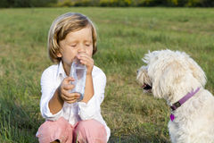 Young boy drinking water outdoors Stock Image